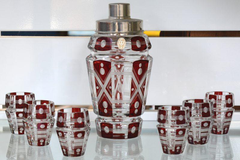 Een shaker en zes glaasjes van kleurloos en rood Boheems kristal.