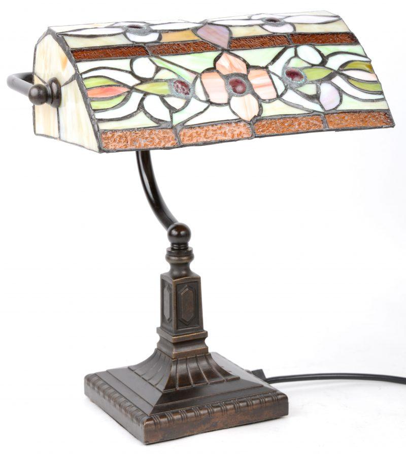 Een oude bronzen bureaulamp met een kapje van glas in lood in de stijl van Tiffany.