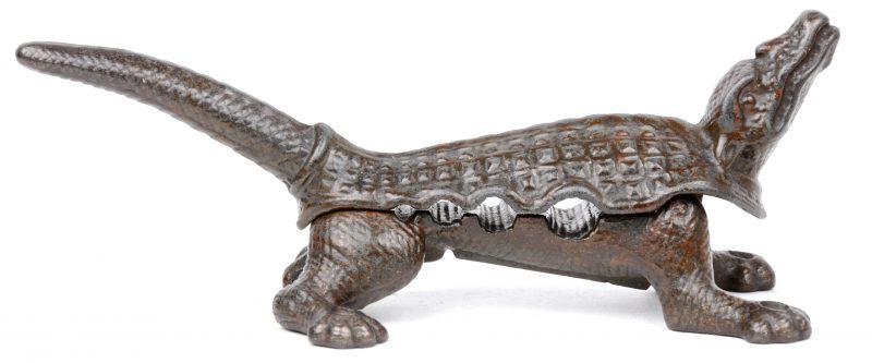 Een gietijzeren stoppenverkleiner in de vorm van een krokodil. Onderaan gemerkt.