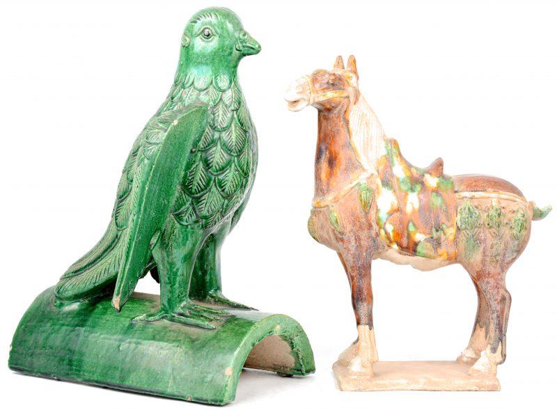 Een paard van meerkleurig geglazuurd Chinees aardwerk naar een voorbeeld uit de T'ang en een vogel van groen geglazuurd aardewerk.