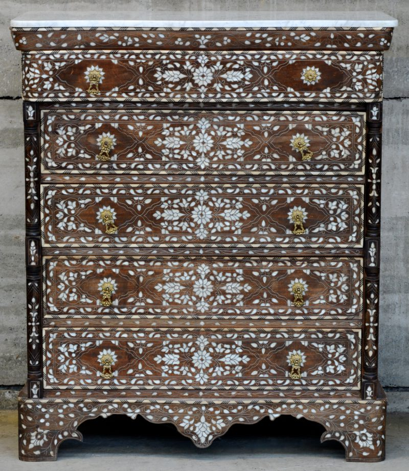 Een hardhouten commode met vijf laden en een marmeren blad, versierd met ingelegde motieven van parelmoer en details van ivoor en ebbenhout.