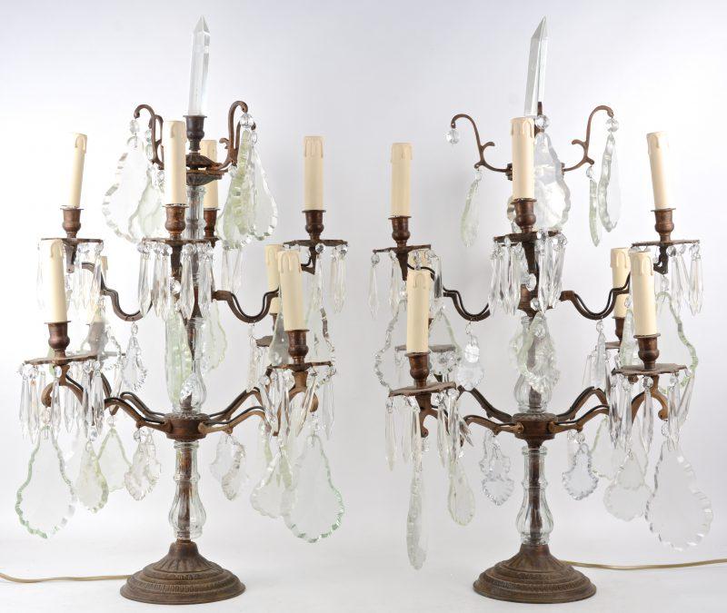 Een paar bronzen girandoles met acht lichtpunten in twee niveau en versierd met kristallen pendeloques. Gemonteerd op elektriciteit.