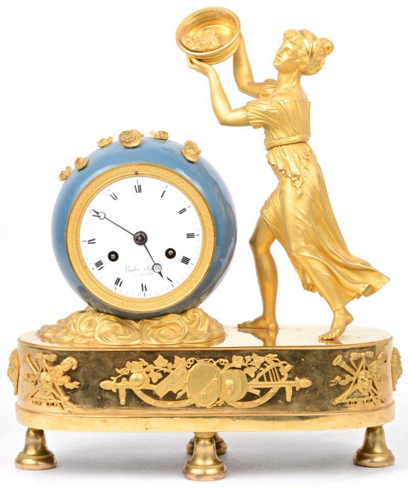 Een vergulde schouwpendule met bol uurwerk in blaugelakte kast en getooid met een jonge vrouw met bloemenmand.