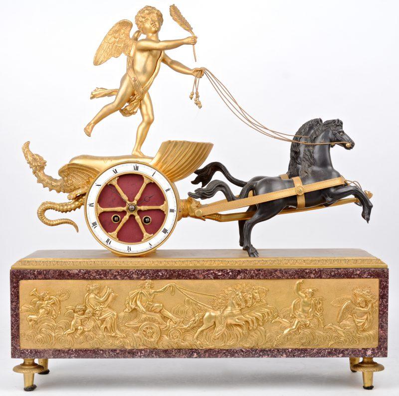 Een vergulde schouwpendule met een reliëfdecor van classicistische figuren met een strijdwagen. De pendule als wiel van een strijdwagen met tweespan, versierd met een draak en bestuurd door een engel.