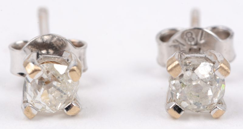 Een paar 18 karaats wit gouden oorbellen bezet met diamanten met een gezamenlijk gewicht van ± 0,40 ct.