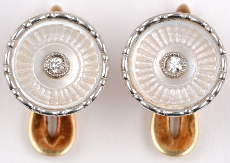 Een paar 18 karaats wit en geel gouden manchet knopen bezet met twee kleine briljantjes.