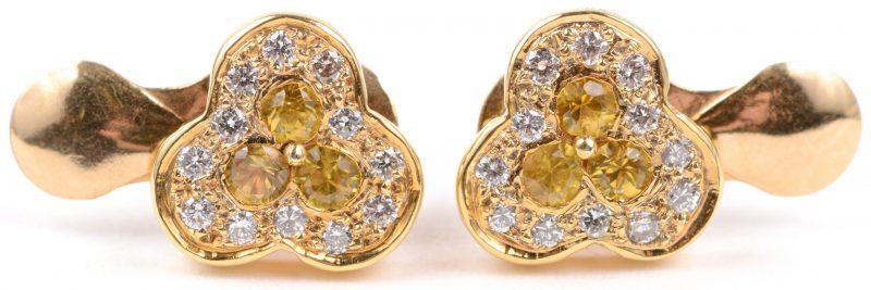 Een paar 18 karaats wit gouden oorbellen bezet met briljanten met een gezamenlijk gewicht van ± 0,50 ct. een gele saffieren met een gezamenlijk gewicht van ± 0,30 ct.