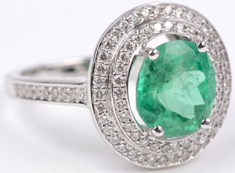 Een 18 karaats wit gouden ring bezet met diamanten met een gezamenlijk gewicht van ± 0,55 ct. en een Colombiaanse smaragd van ± 2,20 ct.