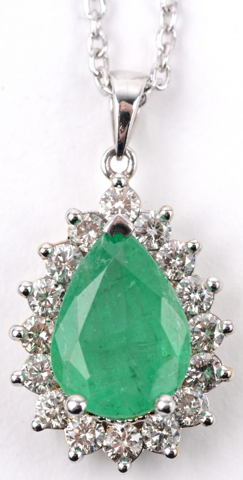 Een 18 karaats wit gouden ketting met hanger bezet met diamanten met een gezamenlijk gewicht van ± 0,80 ct. en een druppelvormige smaragd van ± 2,30 ct.