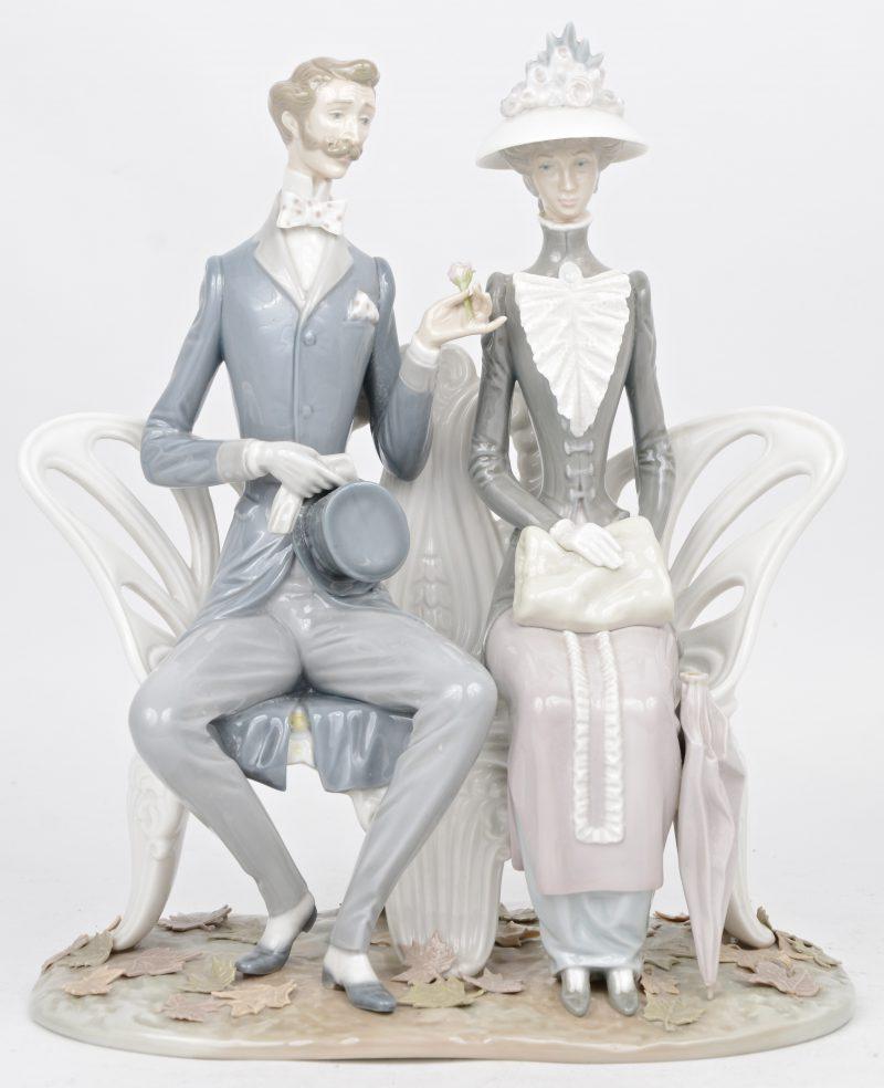 Een verliefd burgerpaar op een bank. Groep van meerkleurig porselein. Onderaan gemerkt. Handvat van parasol ontbreekt.