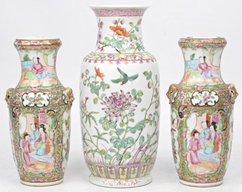 Een paar kleine vaasjes van Canton porselein (H. 19 cm, schilfer aan een rand, haarscheur in beide) en een vaasje van Chinees porselein met een famille rose decor van bloemen en vogels (H. 23 cm).