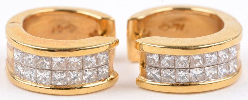 Een paar 18 karaats geel gouden oorbellen bezet met diamanten princess cut met een gezamenlijk gewicht van ± 0,78 ct.