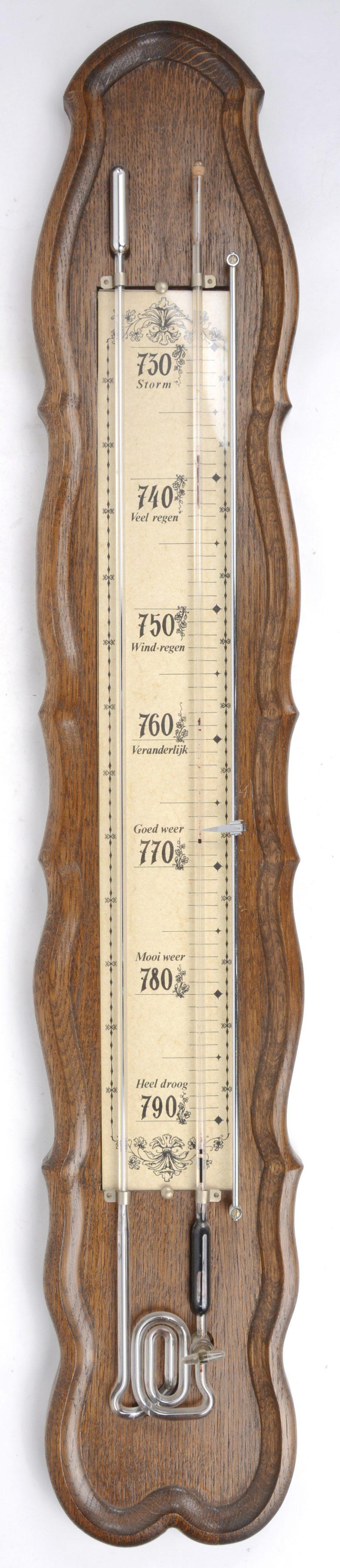 Een barometer op eikenhouten plank.