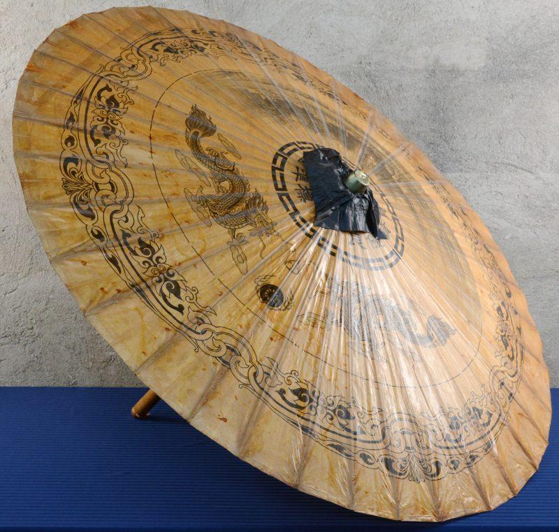 Een Chinese parasol van hout en papier met een decor van draken en een landschap.