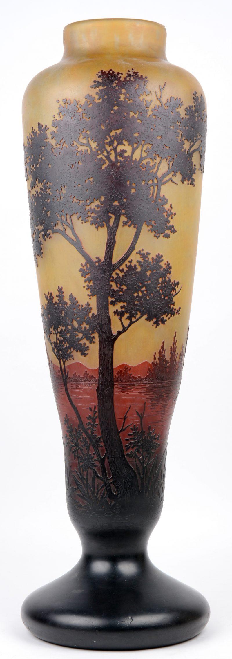 Een grote glazen vaas met een met het wiel gegraveerd landschapsdecor op een oranjebruine achtergrond, eindigend in een donkere voet. Voluit gemerkt en met het kruis van Lotharingen. Begin XXe eeuw.
