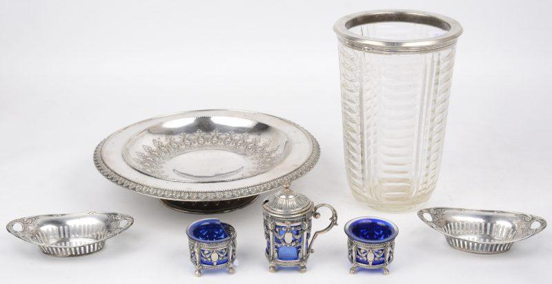 Een lot zilver, bestaande uit een tazza, twee kleine mandjes, een kleurloze vaas met zilveren montuur, peper- en zoutpotjes en een mosterdpotje met blauw glazen recipiënten. Eén gebroken. Duitse en Belgische keuren.