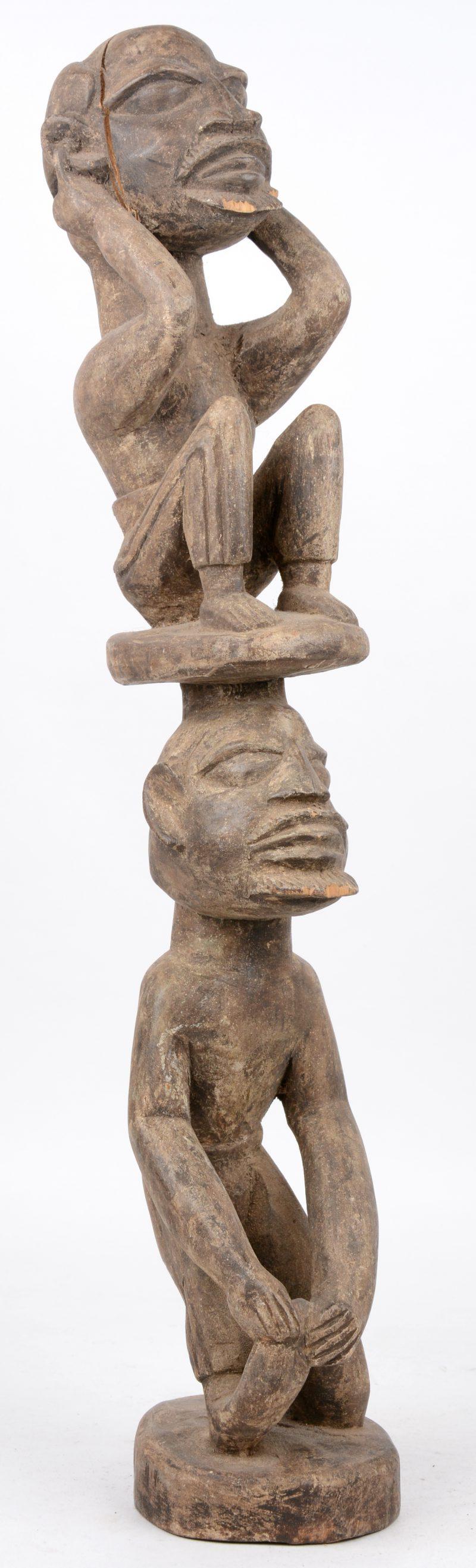 Een Afrikaans houten beeld met twee op elkaar geplaatste figuren. DRC.