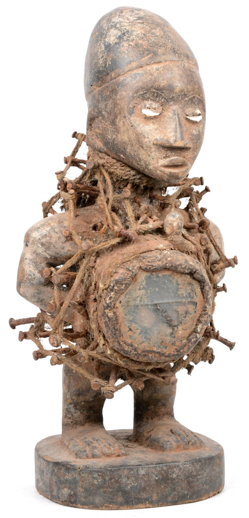 Een Afrikaans houten beeld voorzien van een ruitje en spijkers en met schelpen als ogen.