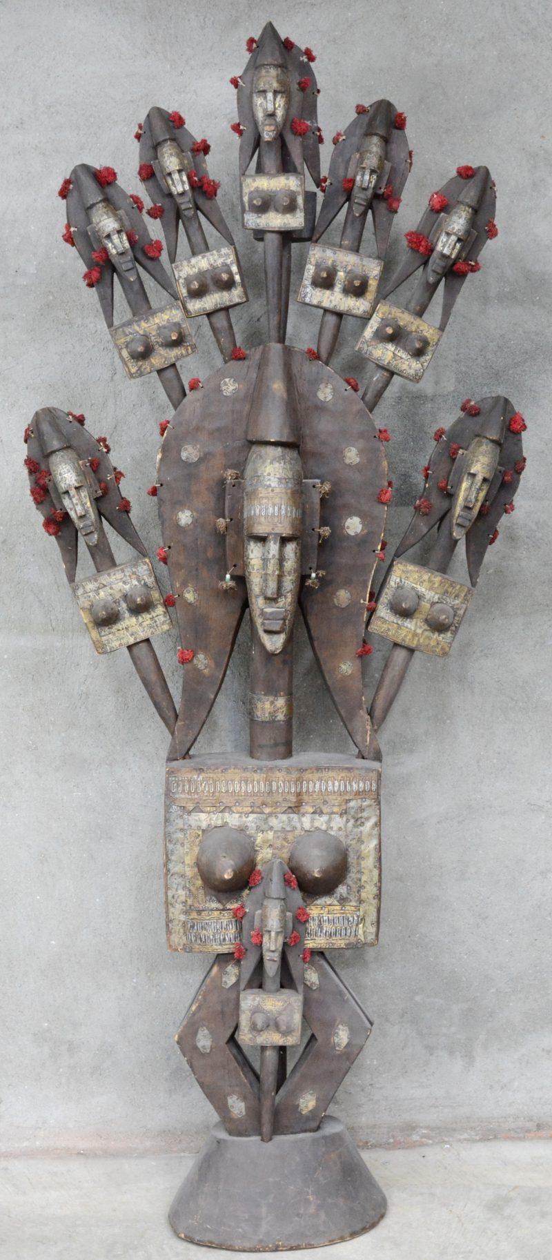 Matriarchale stamboom van hout en metaal. Een groot vrouwelijk beeld voorzien van negen losse, al dan niet dubbele hoofden. Bamana Bambara (Mali).