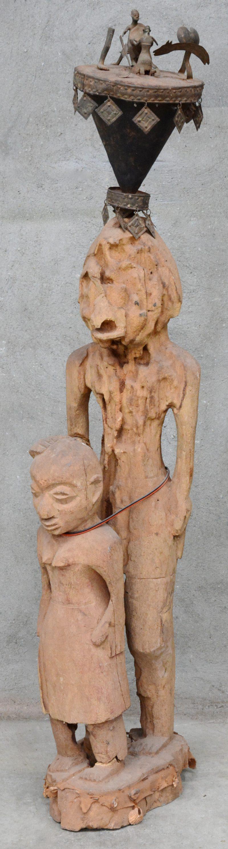 Bovenstuk van ee Dogon staf van ijzer en brons, gemonteerd op een verweerd houten beeld van een ouder met kind.