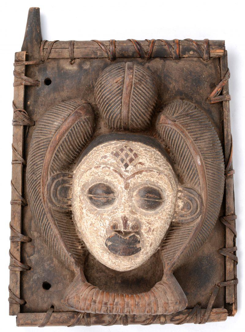 Een houten deurtje in hoogreliëf versierd met een hoofd in de geest van de Punu maskers. Afrikaans werk.