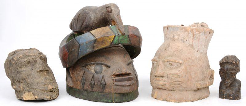 Een polychroom houten helmmasker getooid met een vogel (H. 23 cm), één niet gekleurd helmmasker (H. 17 cm) en twee houten hoofdjes (12 & 10 cm). Afrikaans werk.
