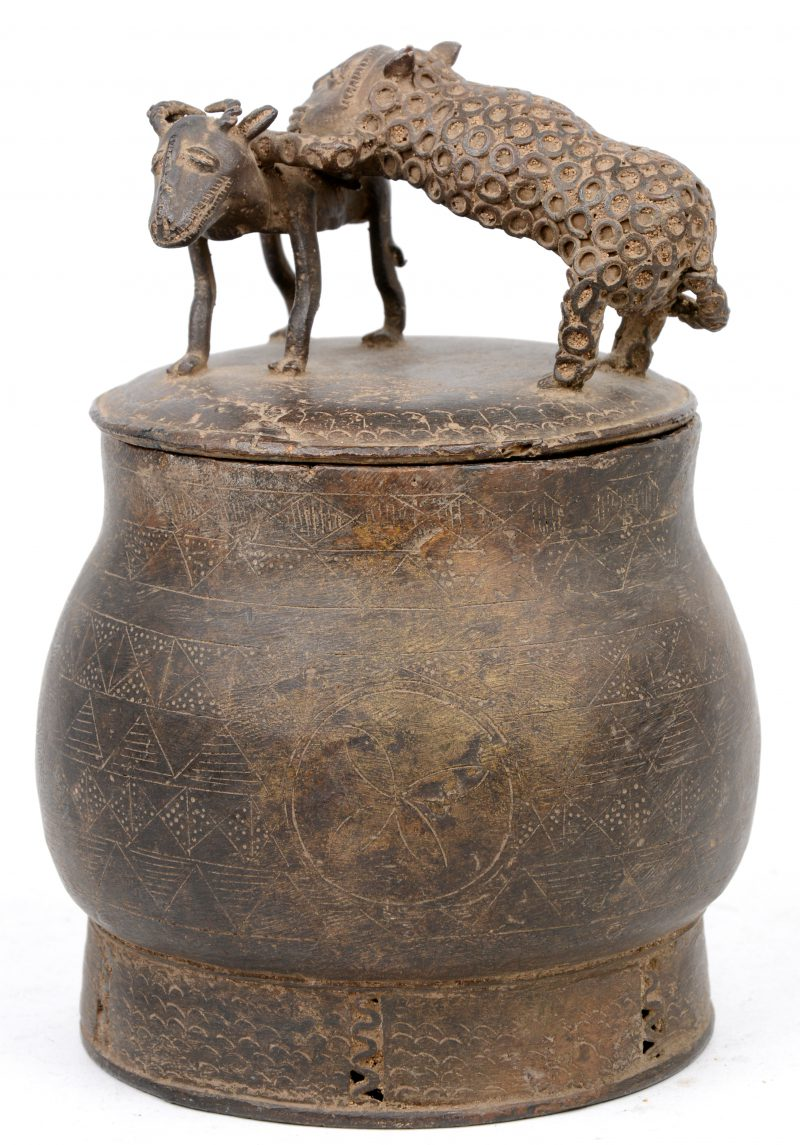 Een voorraadpot van geciseleerd brons, op het deksel een luipaard die een geit aanvalt. Verloren was techniek. Benin.