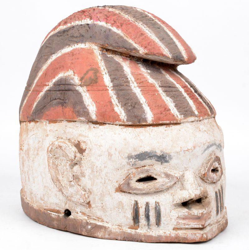 Een polychroom houten helmmasker met een Portugese muts. West-Afrika.