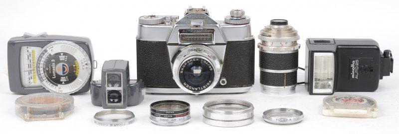 Een oude fotocamera met vijf lenzen van Voightländer en drie anderen. Eveneens een flash en lichtmeter.