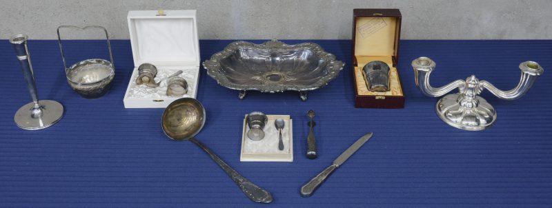 Een lot verzilverd metaal, bestaande uit een milieu-de-tabe, een enkele en een dubbele kandelaar, een pollepel, een suikertang, een mandje, een mes, een doopbekertje en twee geboortesets.