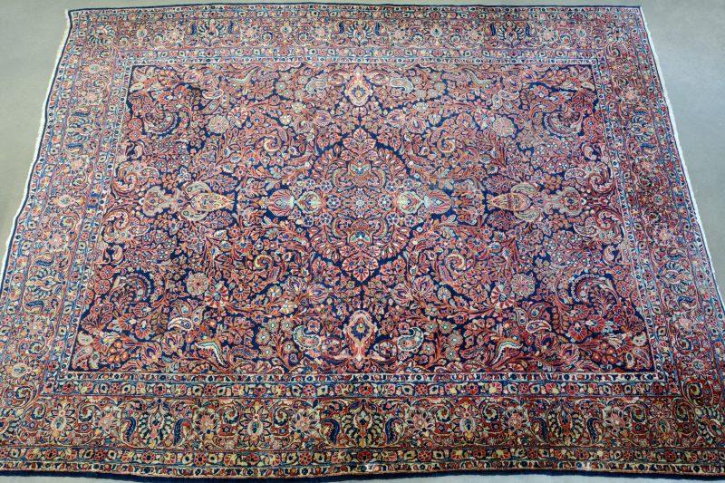 Een handgeknoopt Perzisch wollen tapijt, gedecoreerd met bloemenmotieven. slijtage.