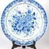 Grote schotel van blauw en wit aardewerk met bloemendecor. Achteraan gemerkt: Delft Royal Gouda Holland en genummerd 2965/40. Evenals een kalebasvormige vaas met blauw en wit decor, gemonteerd als lamp, onderaan gemerkt: Deflt.