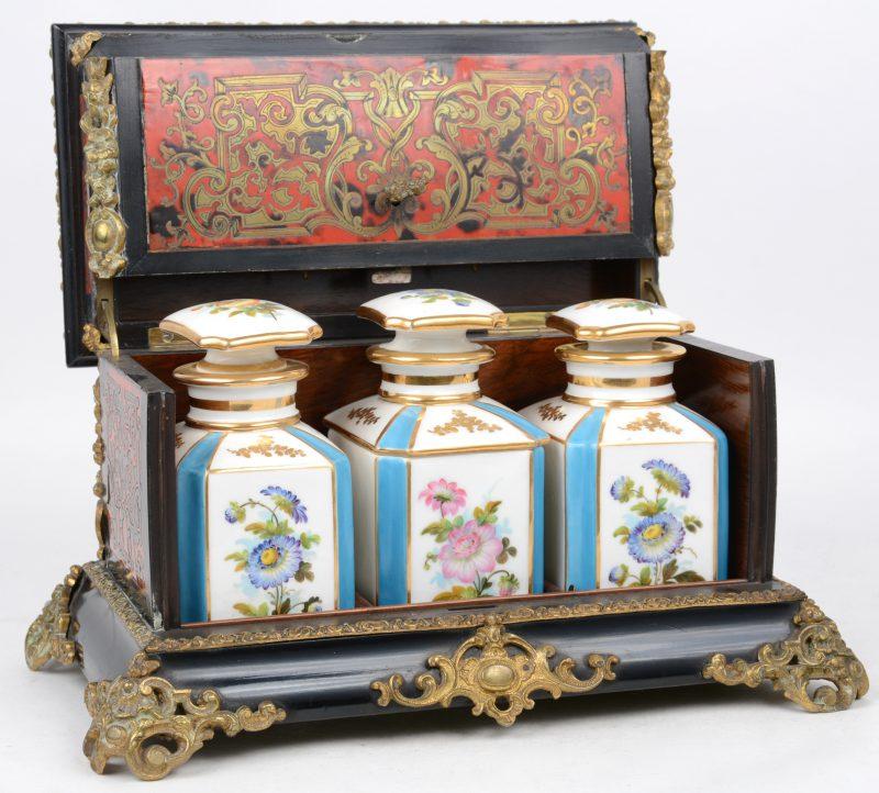 Een kistje van zwartgelakt hout, versierd met boullemarquetterie van messing en schildpad en met bronsbeslag. Binnenin twee porseleinen flesjes en een dekseldoosje met meerkleurige en vergulde decors. XIXe eeuw.