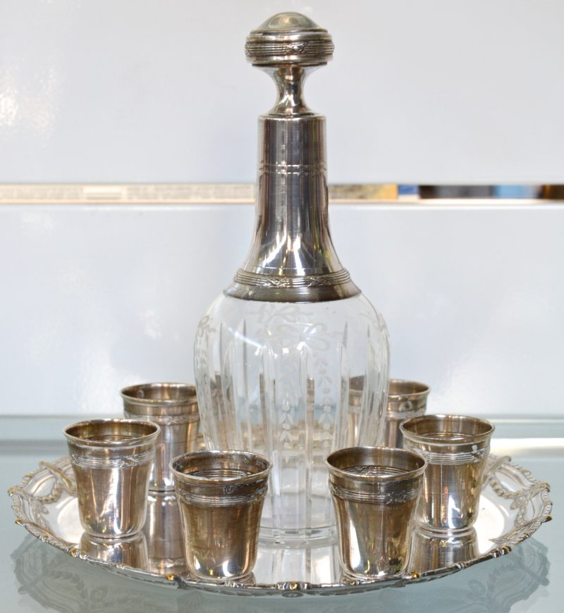 Een likeurkaraf in geslepen en gegraveerd kristal met zilveren montuur en zes kleine zilveren  gobelets, samen op verzilverd schaaltje van WMF.