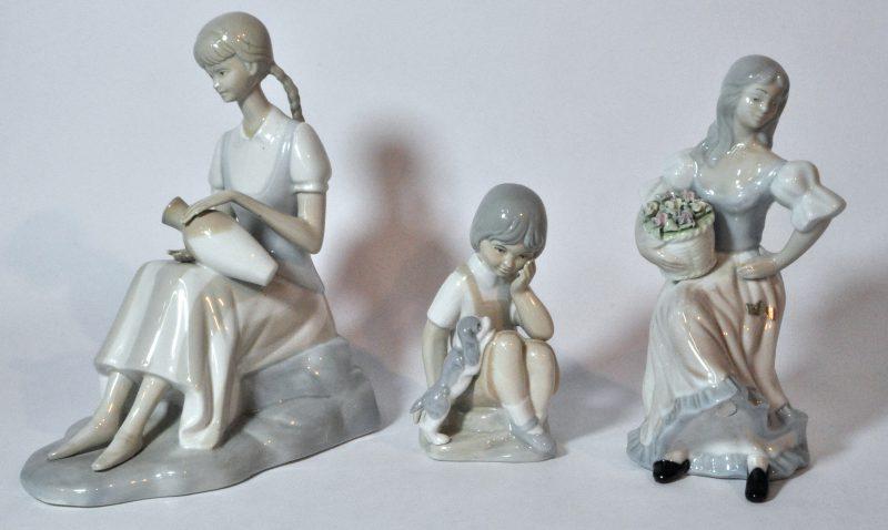 Een lot van drie beeldjes van meerkleurig porselein in de stijl van Lladro. Reparatie aan één van de voetjes.