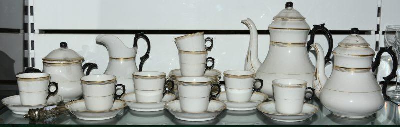Een theeservies van wit, zwart en verguld porselein, bestaande uit een koffiepot, theepot, melkkannetje, suikerpot, acht kopjes en twaalf onderbordjes. We voegen er een zilveren suikertang aan toe.