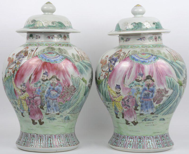 Een paar dekselvazen van meerkleurig Chinees porselein met een famille-rosedecor van krijgers. Onderaan gemerkt.