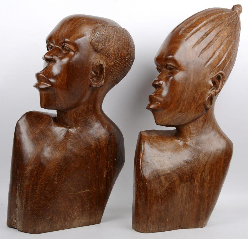 Een vrouwen- en mannenbuste van gesculpteerd hout. Afrikaans werk. Eén oor beschadigd.