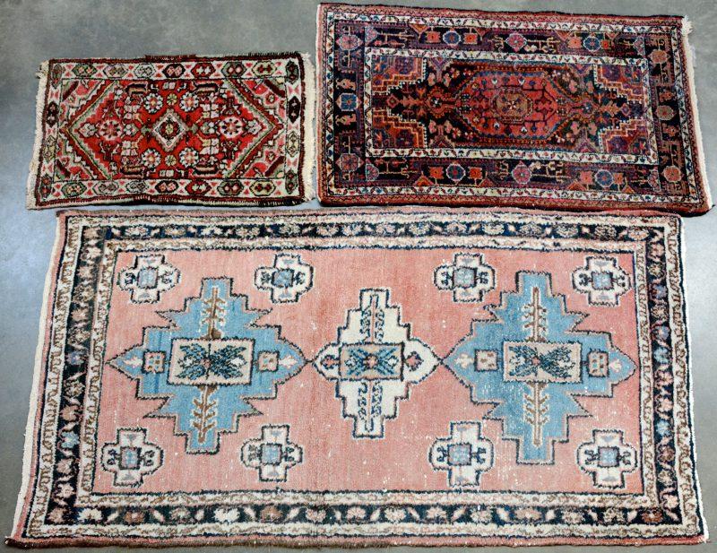 Een lot van drie handgeknoopte Perzische wollen tapijtjes.