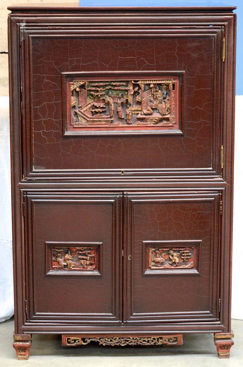 Een Chinees televisiemeubel van roodgelakt hout met twee kleine paneeldeuren onder een grote, telkens versierd met een uitgestoken decor van personages.