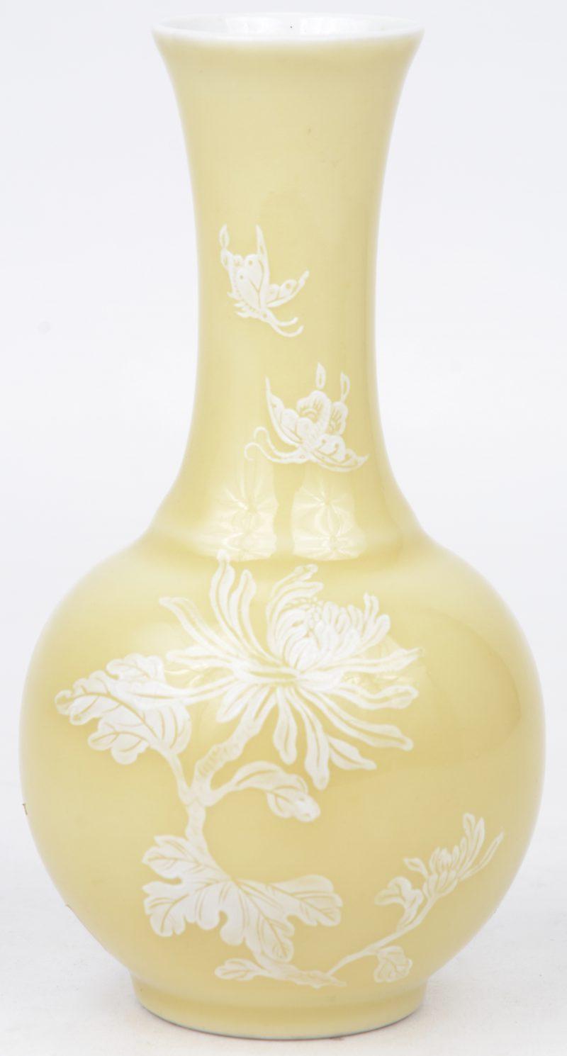 Een klein balustervaasje van Chinees porselein met een wit decor van bloemen en vlinders op gele fond. Onderaan gesigneerd.