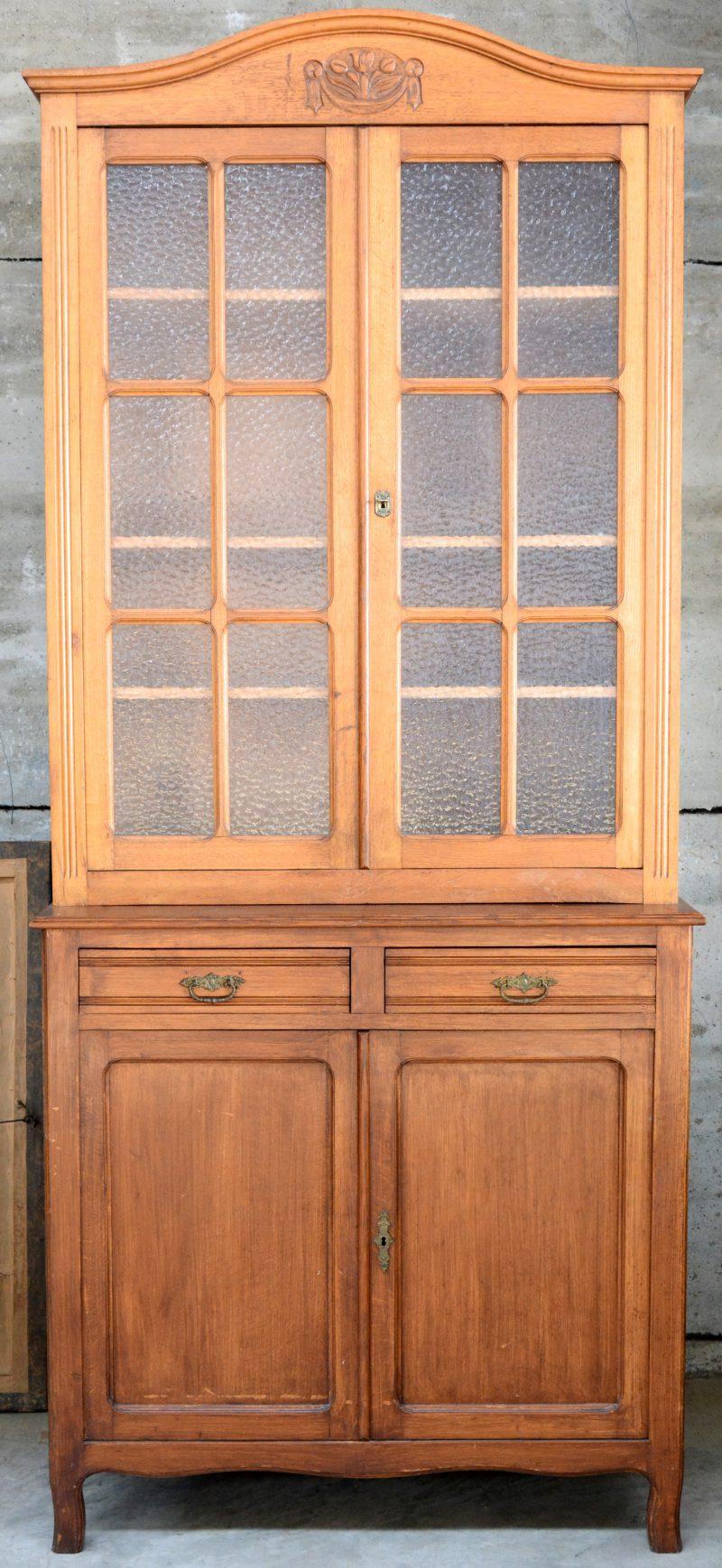 Een sobere tweeledige vitrinekast met onderaan twee deuren en twee laden en bovenaan twee gevitreerde deuren.