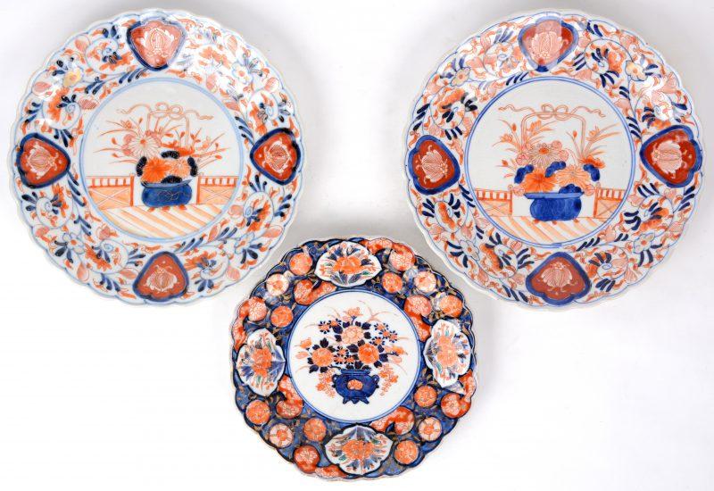 Een paar borden van Imari-porselein met geribde vleugel en een decor van een cachepot met bloemen op het plat. We voegen er een kleiner, gelijkaardig bordje aan toe.