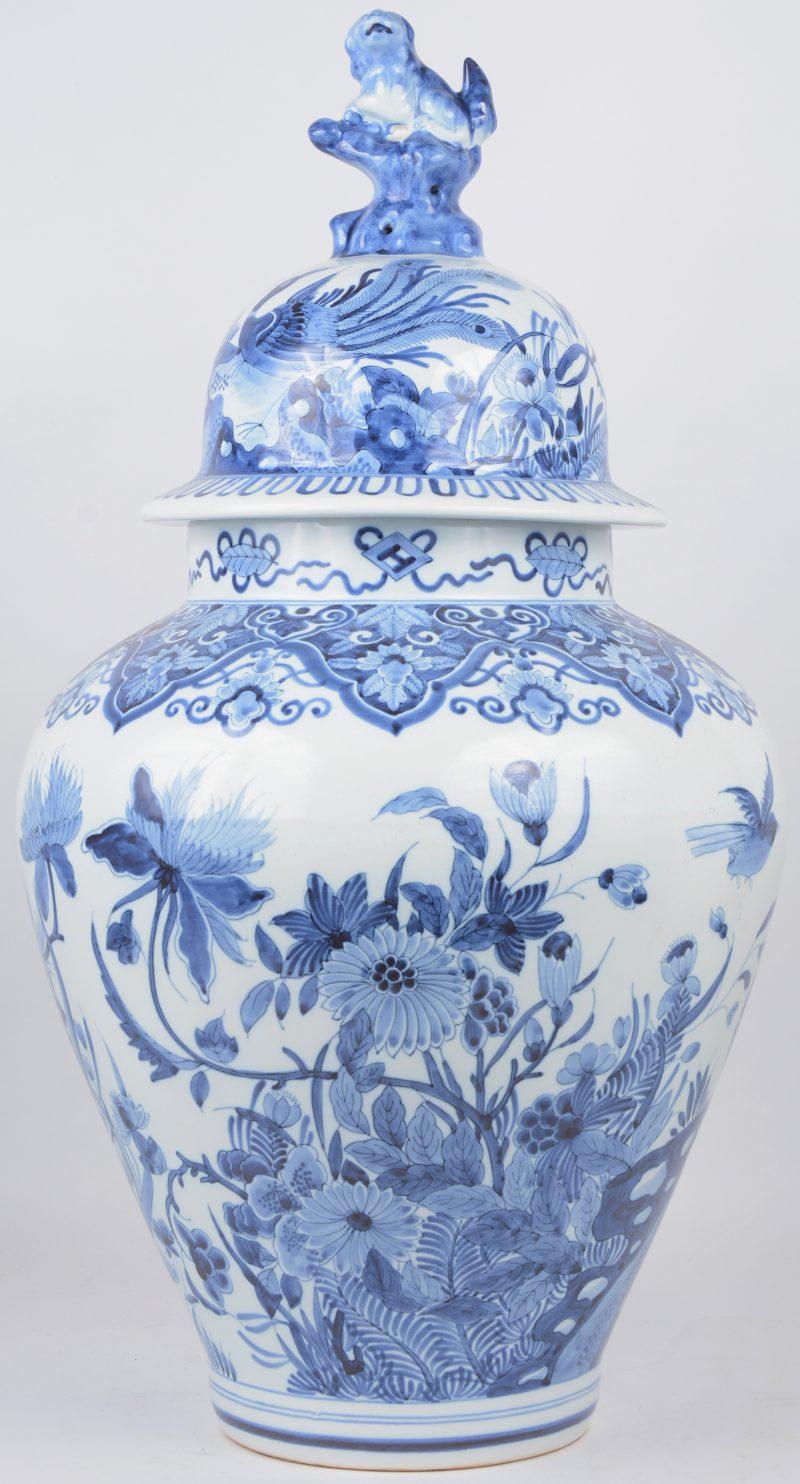 Een dekselvaas van Delfts aardewerk, versierd met een blauw en wit decor van bloemen en vogels en bovenaan getooid met een tempelleeuw. Onderaan gemerkt.