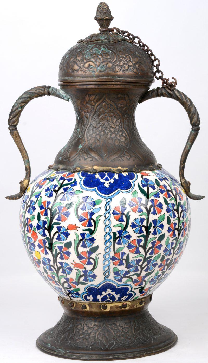 Een dekselvaas van meerkleurig aardewerk met voet, monturen en deksel van gedreven koper. Mogelijk Perzisch.