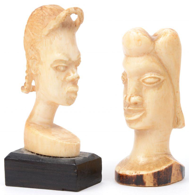 Een paar kleine Afrikaanse vrouwenbustes van gesculpteerd ivoor, waarbij één op ebbenhouten sokkeltje. Begin XXste eeuw.