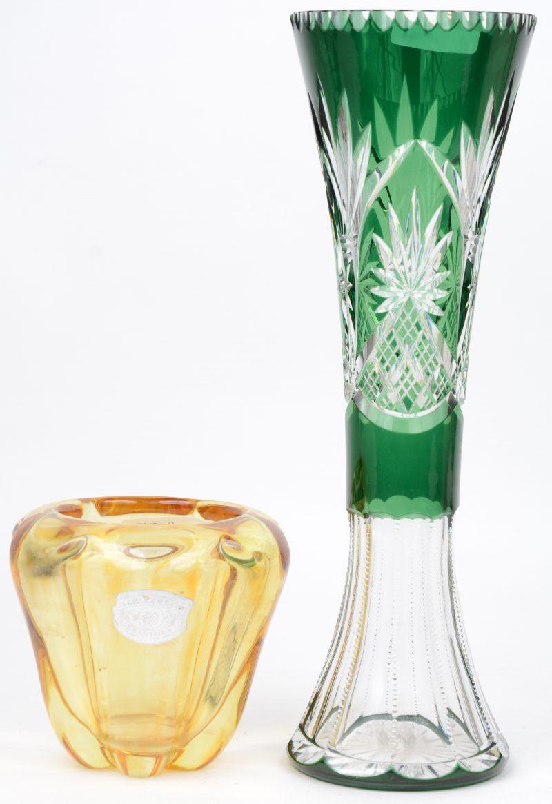 Een lange geslepen groene vaas en een kleine gegoten vaas van geel kristal. De tweede gemerkt van Val St. Lambert.