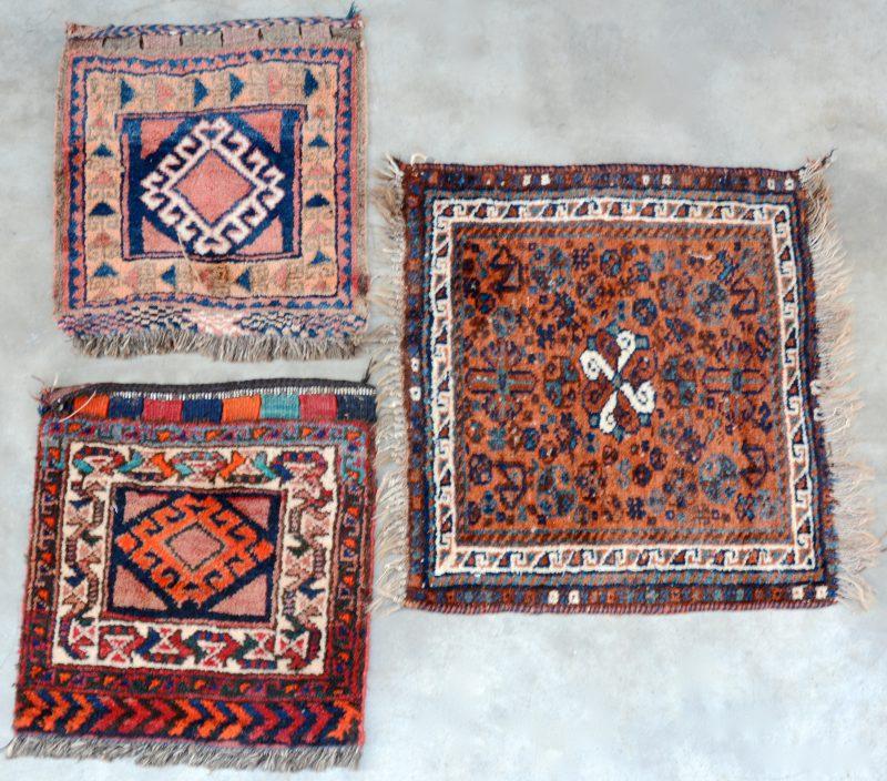 Een lot van drie kleine handgeknoopte Perzische tapijtjes van wol.