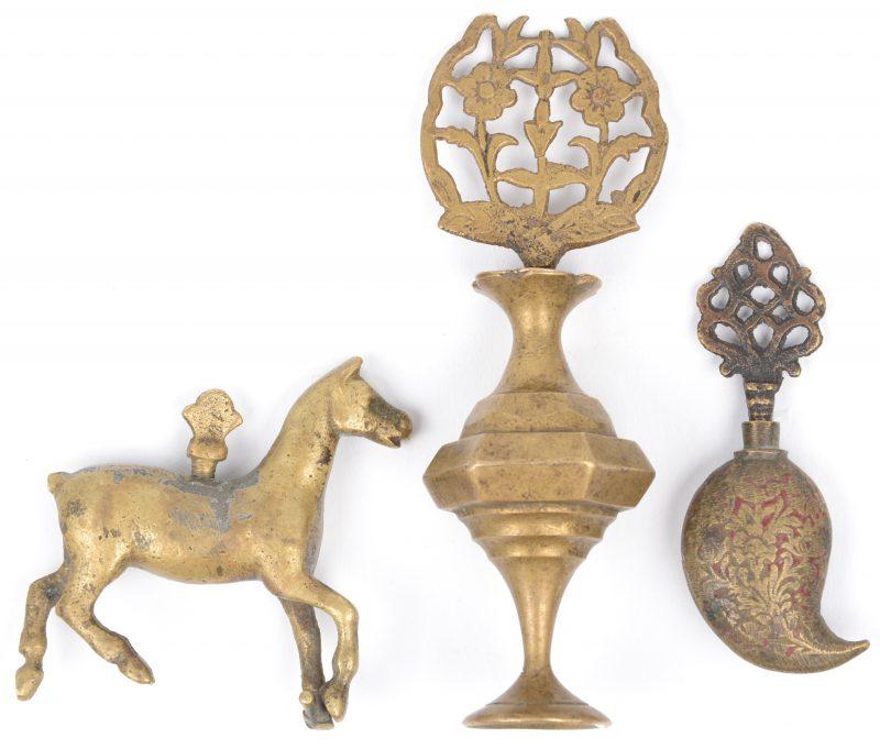 Een lot van drie bronzen snuffbottles, waarbij één in de vorm van een vaasje, het dopje versierd met bloemen, één druppelvormig met opengewerkte dop en met sporen van rode lak en een derde in de vorm van een paard. Indisch werk, omstreeks 1900.