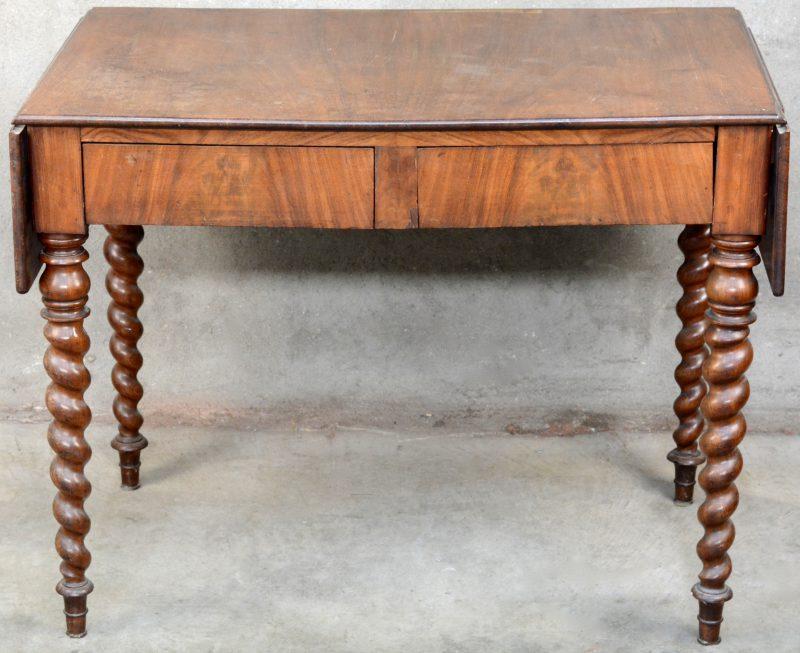Een antieke mahoniehouten tafel met getorste poten, twee neerklapbare uiteinden en twee laden in de gordel. Steunlatjes afgebroken.